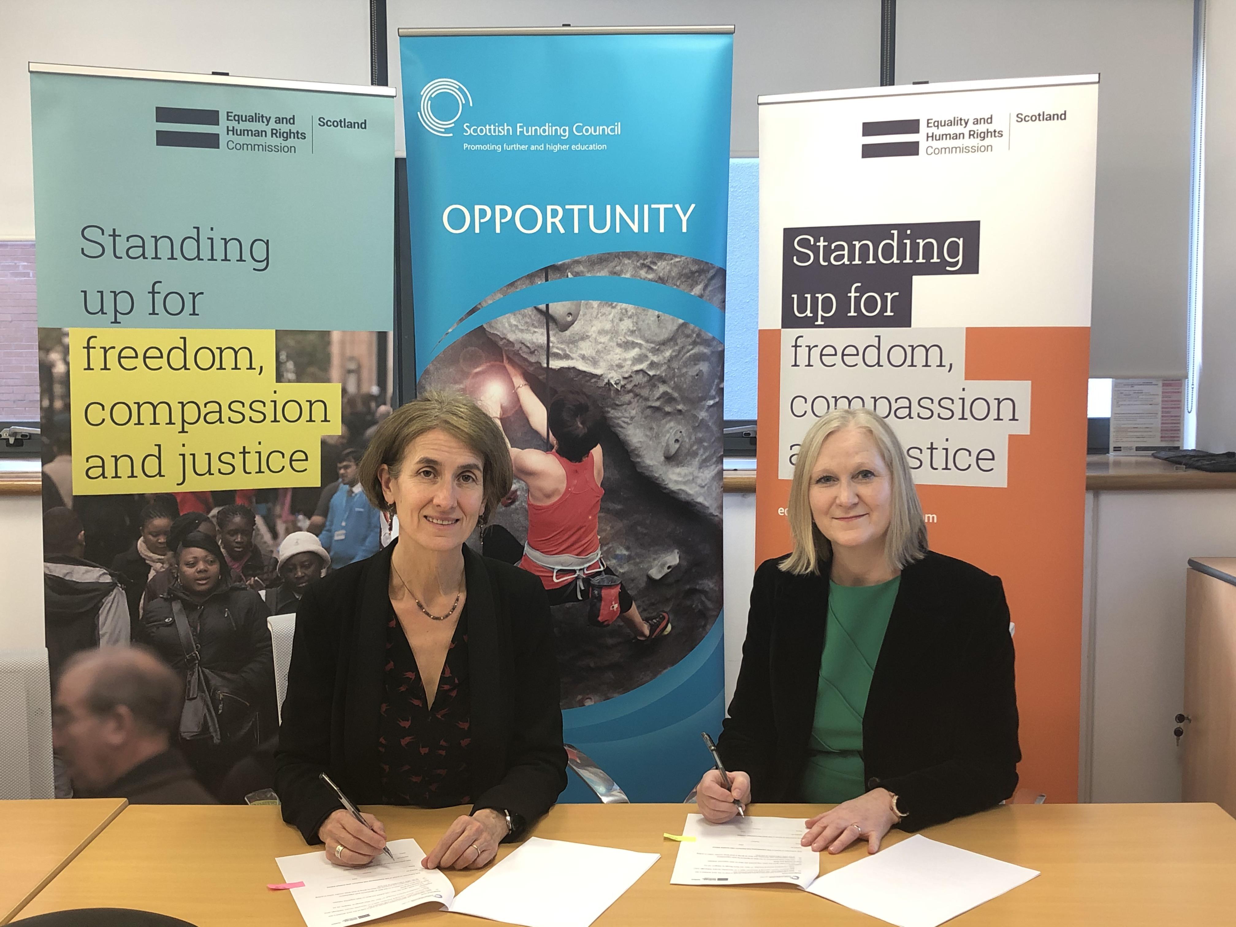Rebecca Hilsenrath (left) and Karen Watt (right) sign the memorandum of understanding