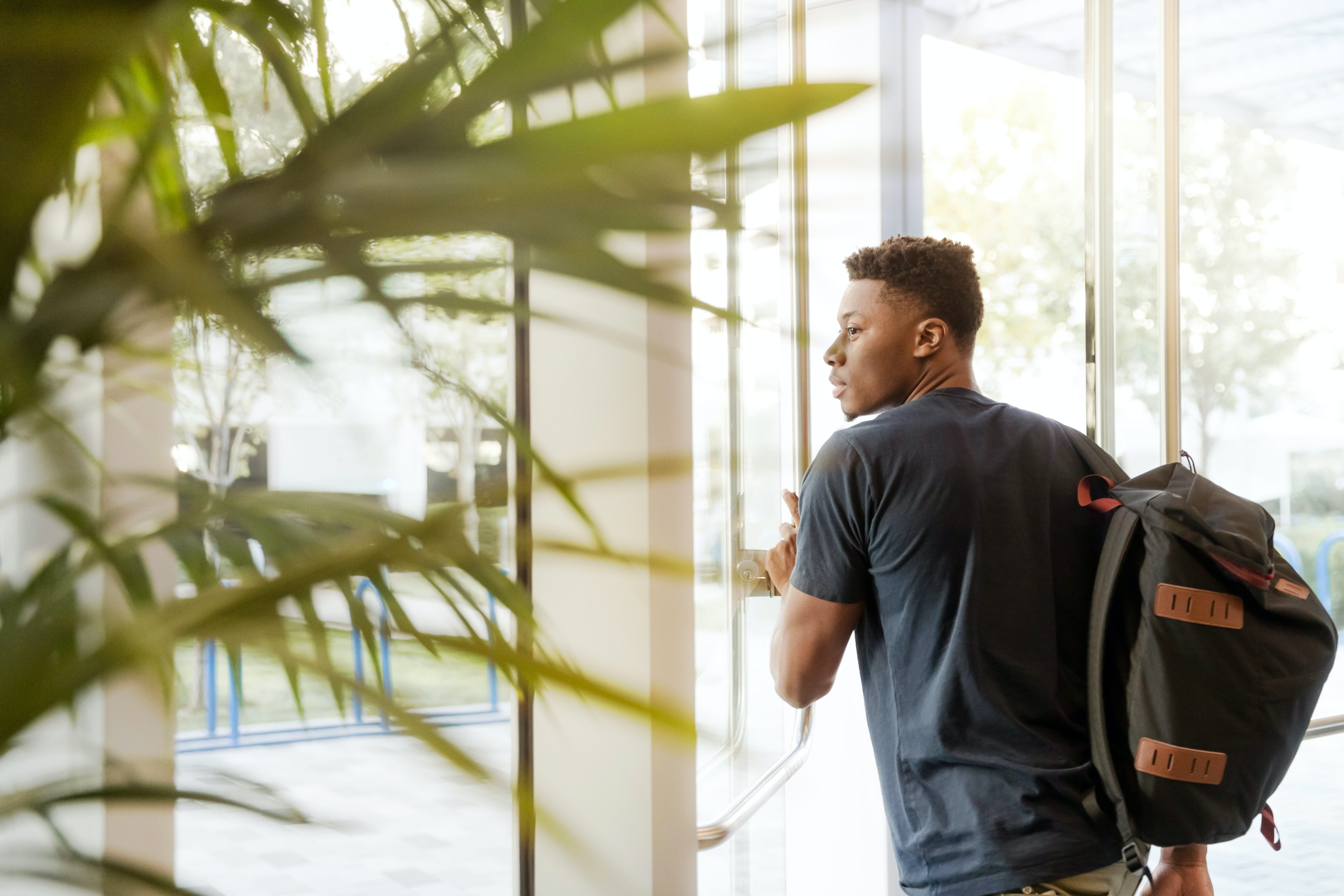 Black university student with backpack.