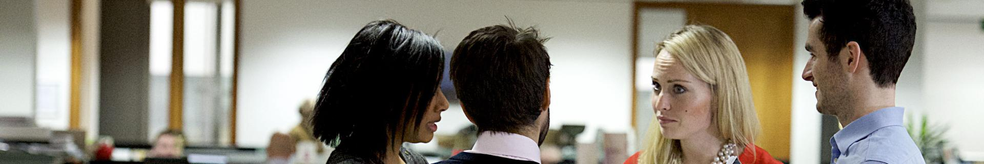 men and women talking in an office