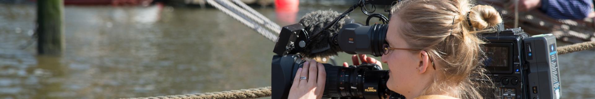 A female reporter operates a television camera