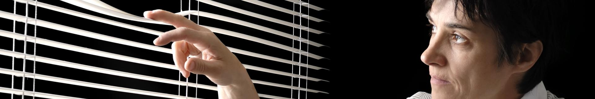 Woman looking through window blinds