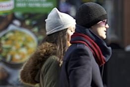 Two people walking on a street