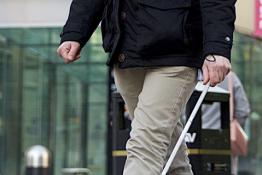 A visually impaired person walking
