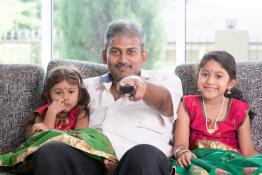 man watching tv with daughters