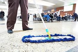 Cleaners' rights: cleaner sweeping the floor in an airport