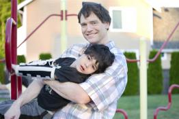 A father with his disabled son in a playground