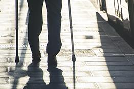 Disabled person with crutches walks beside a bus