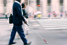 Visually impaired main crossing a road using a walking stick