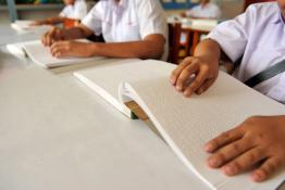 A person tracing their fingers across a Braille book.