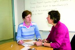 Two women in a meeting room, talking