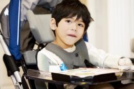 Young disabled boy completing a worksheet