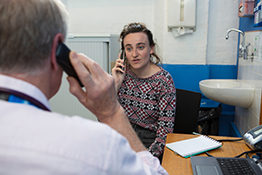 Doctor and patient using a translation service via telephone
