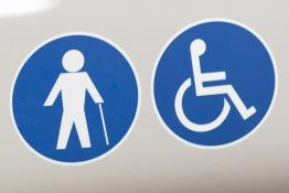 Wheelchair and walking stick stickers on a bus to signify it is accessible for disabled people