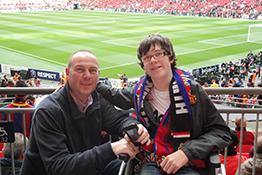 A football fan in a wheelchair with their carer at Wembley Stadium