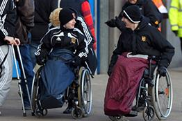 Two football fans in wheelchairs