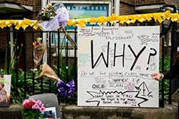 Floral tributes for the Grenfell Tower fire, with a large banner that says 'Why?'