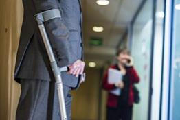 A man on crutches in the workplace