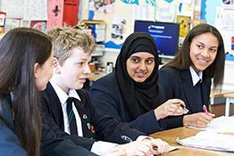 A group of four schoolchildren talk in a classroom