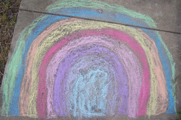 A rainbow drawn in chalk on a pavement