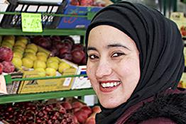 A woman wearing a headscarf working in a grocer's shop