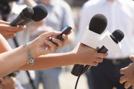 Hands holding microphones and tape recorders at a press conference