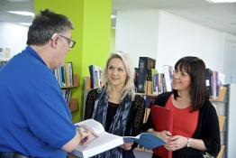 Picture of a deaf man communicating with two women in a library