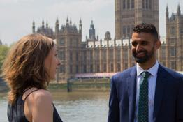 Man and woman talking outside the Houses of Parliament