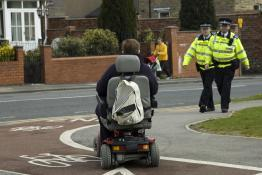Picture of a person using a disability scooter and two police officers walking toward them