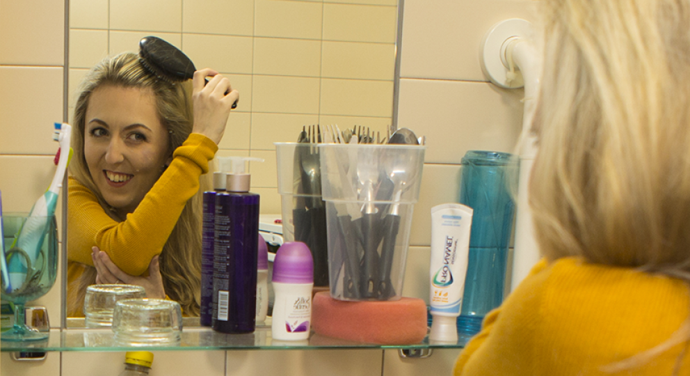 A disabled woman brushes her hair in the mirror of an accessible bathroom