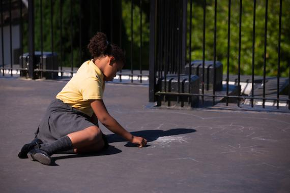 school student writes with chalk on the playground floor